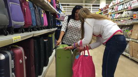 Two womens in a supermarket to buy a suitcase. Select and take one suitcase to store shelves. Two womens in a supermarket to buy a suitcase. Select and take one stock footage