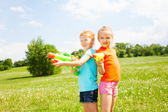 Two wonderful girls play with water guns Royalty Free Stock Images
