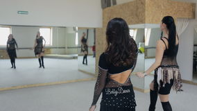 Two wonderful women practice belly dance motions in front of mirror. Females in black fitting transparent suits covered with spangles and pastes exercise on stock video