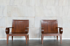 Two wood chair against wall. Stock Photos