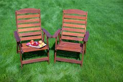Two wood chairs on the grass with vase of flowers Royalty Free Stock Image