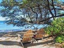 Two wooden Adirondack  chairs overlooking sandy ocean beach Stock Photo