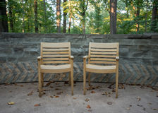 Two Wooden Arm Chairs Against Stone Wall Royalty Free Stock Photos