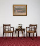Two wooden armchairs, small round coffee table and telephone set Royalty Free Stock Images