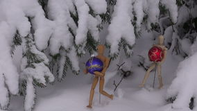 Two wooden artist models holding Christmas baubles. Under snow covered fir tree stock video footage