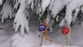 Two wooden artist models holding Christmas baubles. Under snow covered fir tree stock footage