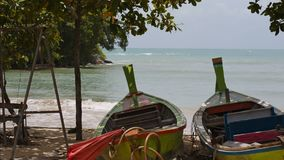 Two wooden asian boats on the sand. Two wooden boats in the shade of the trees on the sand stock footage