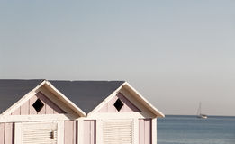 Two wooden bathing boxes and a sailing boat Stock Image