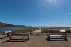 Two wooden benches face a lagoon and beach Royalty Free Stock Photo