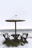 Two wooden benches near river. Covered with snow Stock Photos