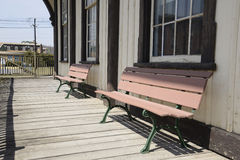 Two wooden benches by an old building royalty free stock image