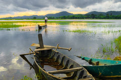 Two wooden boats are anchored, golden hours on the Lak lake Royalty Free Stock Images