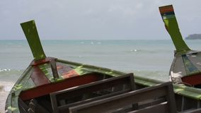 Two wooden asian traditional boats on the sand. Two wooden boats in the shade of the trees on the sand stock video