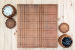 Two wooden bowls with empty go game board. Top view two wooden bowls filled black and white stones with empty go game board on wooden table, traditional chinese Royalty Free Stock Photo