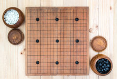 Two wooden bowls with nine handicap stones on go game board. Top view two wooden bowls filled black and white stones with nine handicap stones on go game board Stock Images
