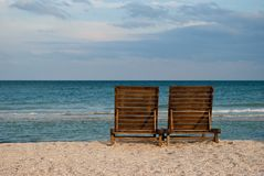 Two wooden brown chaise longue on the beach sand sea shore blue sky wave summer. Two wooden brown chaise longue on the beach on the blue sea shore water blue sky stock photography