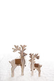 Two wooden carved moose isolated on white snowy background for c Royalty Free Stock Photo