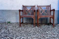 Two wooden chair against a wall with stones on the ground Stock Photo