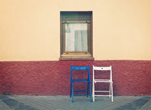 Two wooden chairs below window Royalty Free Stock Photo