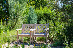 Two Wooden Chairs in Green Garden Stock Photo