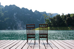 Two wooden chairs on the lake Royalty Free Stock Photo