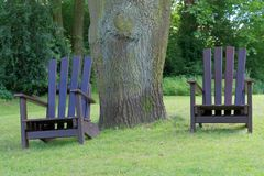Two wooden chairs for relaxing on the green lawn. In a public park. `Planten un Blomen` city garden in Hamburg, Germany royalty free stock images