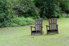 Two wooden chairs for relaxing on the green meadow in a park. Two wooden chairs for relaxing on the green meadow in a public park. `Planten un Blomen` city stock photos