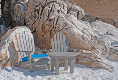 Two wooden chairs and small table at crystal sand of white marbl Royalty Free Stock Images