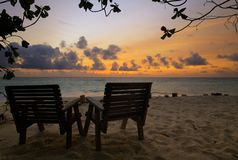 Two wooden chairs on a tropical beach during sunset, low key light Royalty Free Stock Images