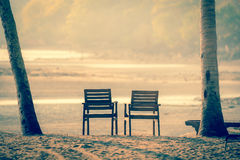 Two  wooden chairs on a tropical beach during sunset. - Moon and Stock Images