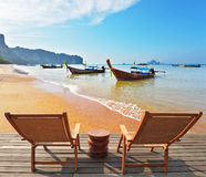 Two wooden chaise lounges and  native boats Royalty Free Stock Photography