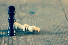 Two wooden chess kings pieces fighting on wooden table. Royalty Free Stock Photography