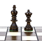 Two wooden chess pieces alone on a chess board. Royalty Free Stock Images