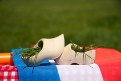 Two wooden clogs on a Dutch flag Stock Photos