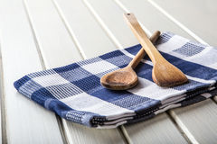 Two wooden cooking spoons on blue towel on wooden table. Stock Photo