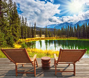 Two wooden deckchairs on the shore of lake Royalty Free Stock Images