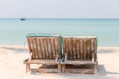 Couple of wooden beach chairs on a tropical sand beach overlooking the sea water and yacht. Thailand Royalty Free Stock Images