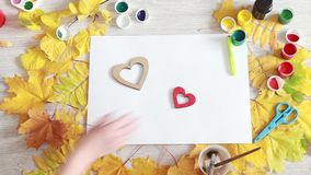 Two wooden decorative heart. Love after separation. Human Hands bring together two decorative wooden heart on a table with autumn leaves and watercolor paints stock footage