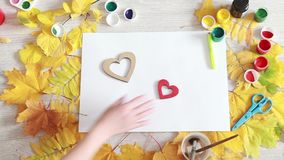 Two wooden decorative heart. Love after separation. Human hands combine the two decorative wooden heart on a table with autumn leaves and watercolors. The stock footage