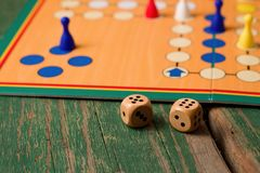 Two wooden dices in front of ludo with figurines. Horizontal photo of Two wooden dices in front of ludo with figurines. Dices have numbers five and six up and Royalty Free Stock Photo