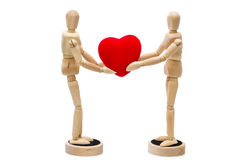 Two wooden dolls, mannequins holding red heart over a white back Royalty Free Stock Image