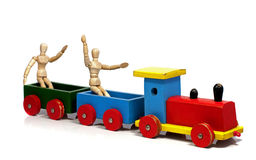 Two wooden dolls sitting on a train Royalty Free Stock Images