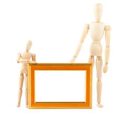 Two wooden dummy and empty frame Royalty Free Stock Photography