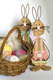 Two wooden Easter bunnies near a wicker basket with three crocheted eggs in front of a bright background. Two wooden Easter bunnies with painted decoration and Stock Photos