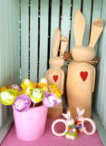 Two wooden easter bunnies with red hearts. A bucket of chickens and two small bunnies Stock Image