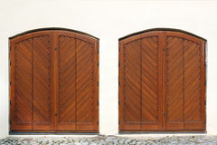 Two wooden entrance gate on white wall Stock Image