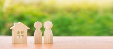 Two wooden figures of people and a house on a nature background. concept of affordable housing, mortgages for buying a home. For young families and couples stock image