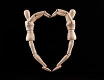 Two wooden figurines forming heart shape - love and relationship Stock Photography