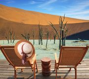 Two wooden folding chairs - deck chairs on a wooden platform. Ecotourism in Namib-Naukluft National Park, Namibia. The bottom of. Dried lake Deadvlei, with dry royalty free stock photos
