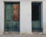 Two wooden green blue blue   Georgian style font doors to homes, against a white wall stock images